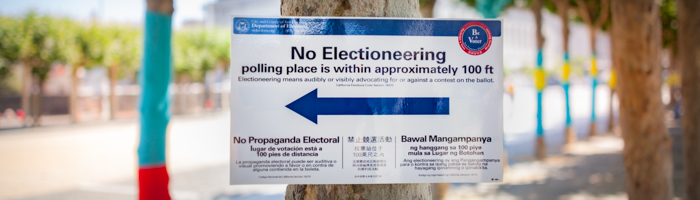 "Sign that reads ""No Electioneering"" posted on a tree 100 feet away from a polling place"