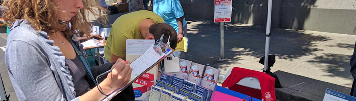People filling out voter registration applications at an Elections Outreach event